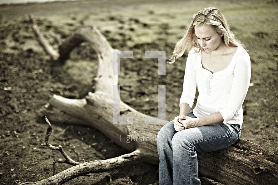 A woman sitting on a log in solitude