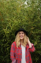 a woman in a hat standing in front of a bush