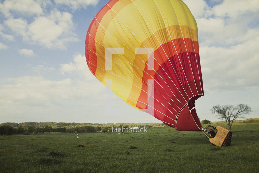 Hot air ballon taking off in a field