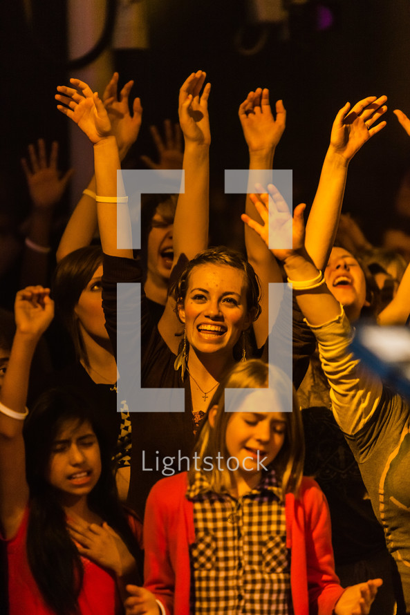 Group worshipping hands raised worship young people youth girl smiling at God