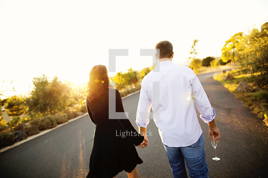 Couple holding hands walking at sunset romance wine glass in hand relationship