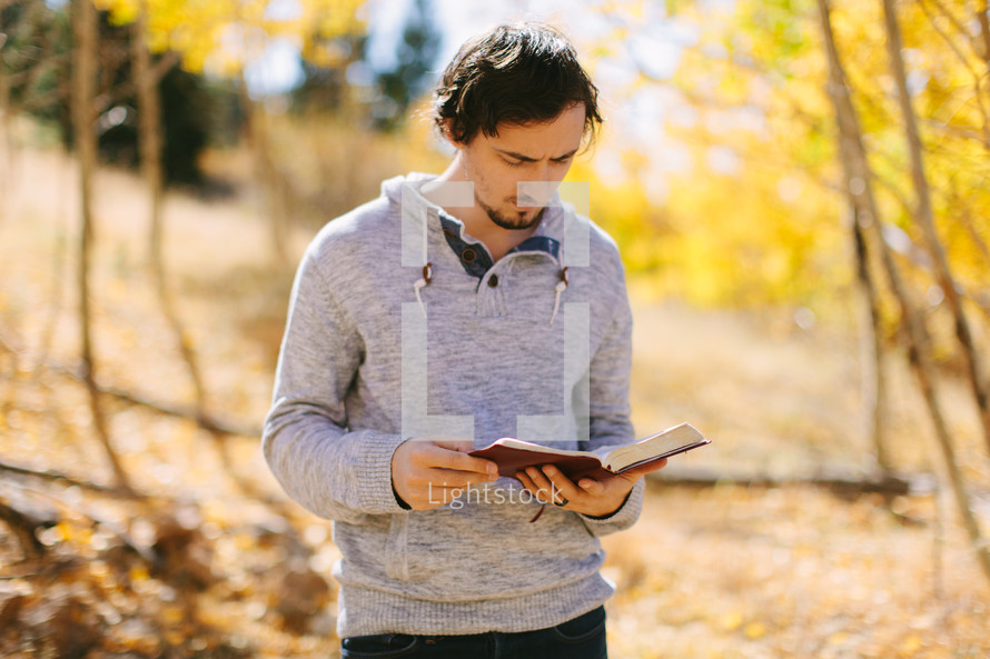a man standing reading a Bible on a fall day