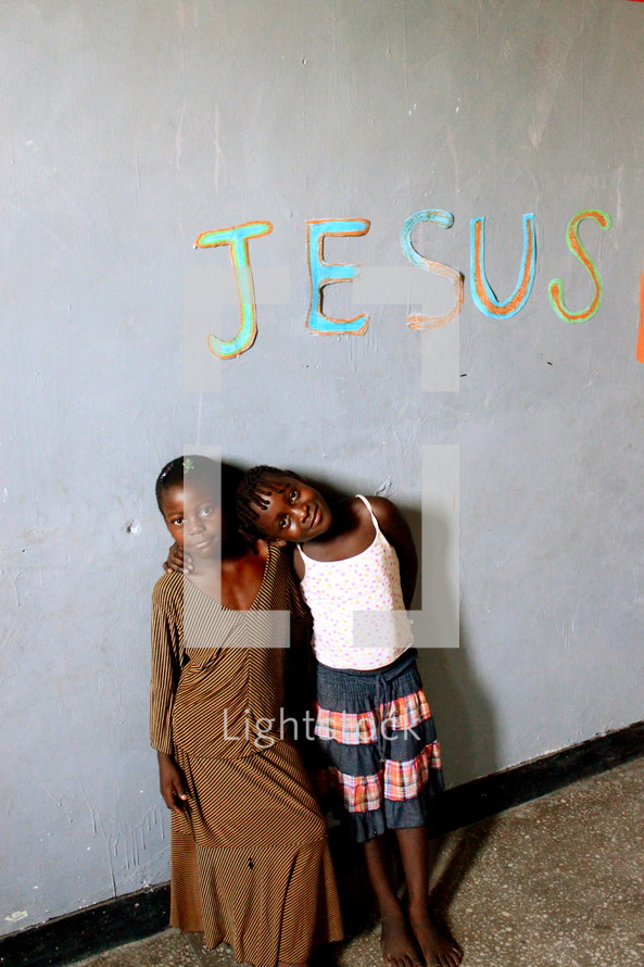 Jesus written on the wall over two children of God