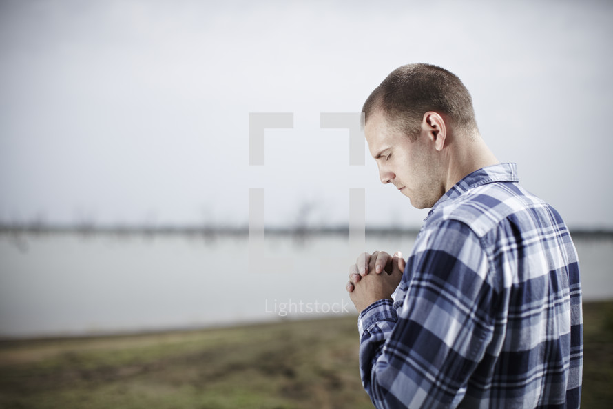 A man praying near water