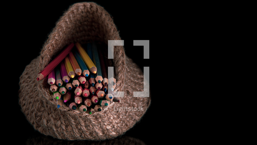 Many colored pencils in a knitted basket on a black background