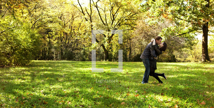Husband and wife kissing in open grass field