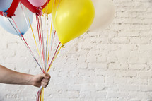 a man holding out balloons