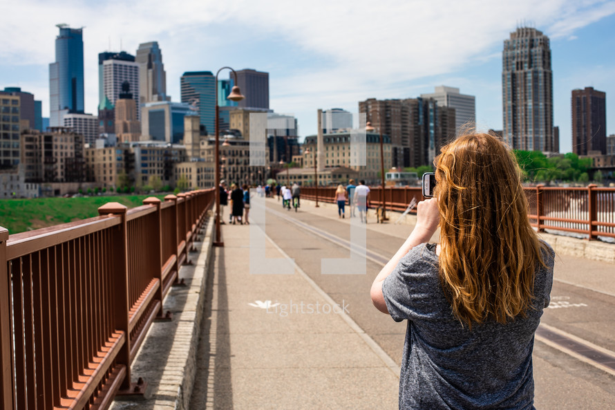 woman taking a picture of a city view