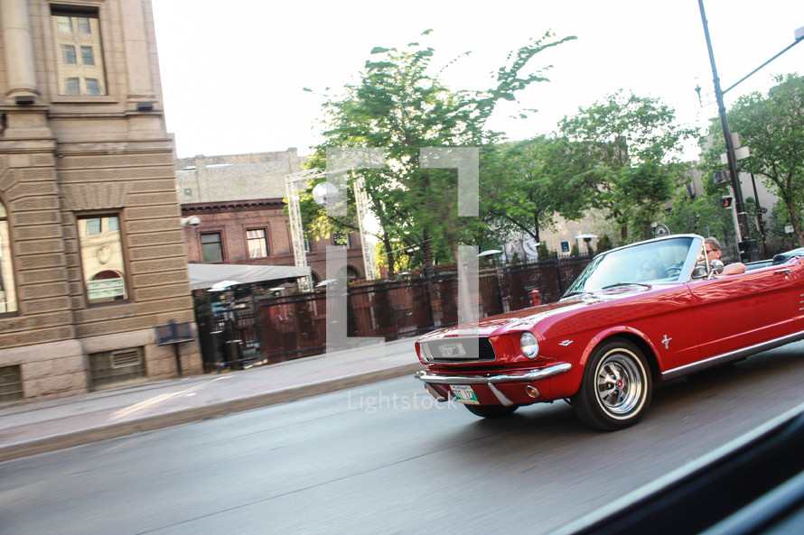 Man driving a classic mustang down the street