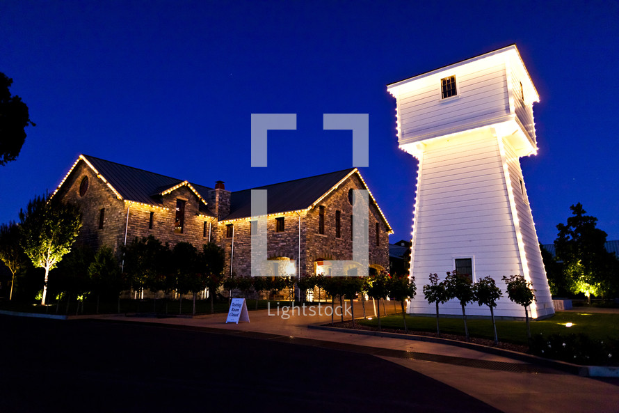 View of winery stone building and white tower at night.