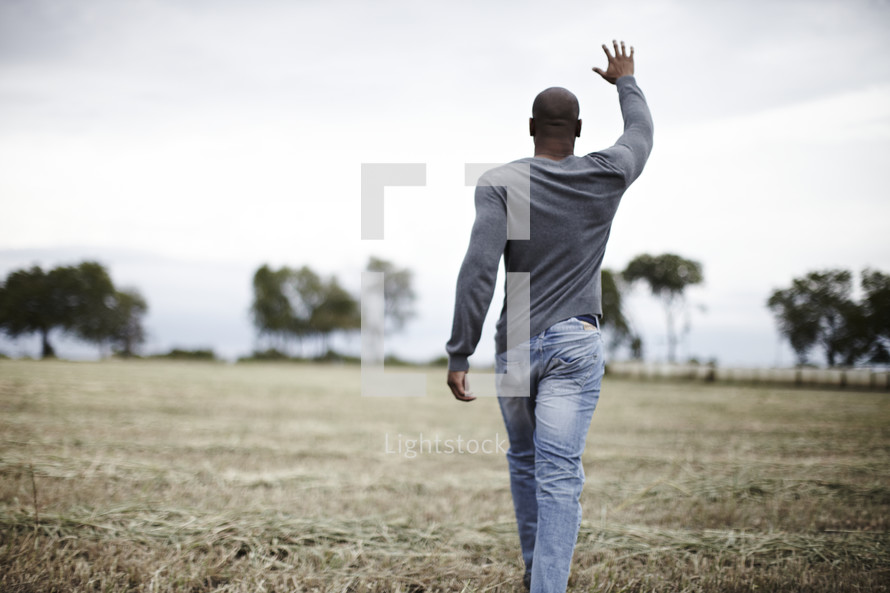 A man walking and praying with a hand raised