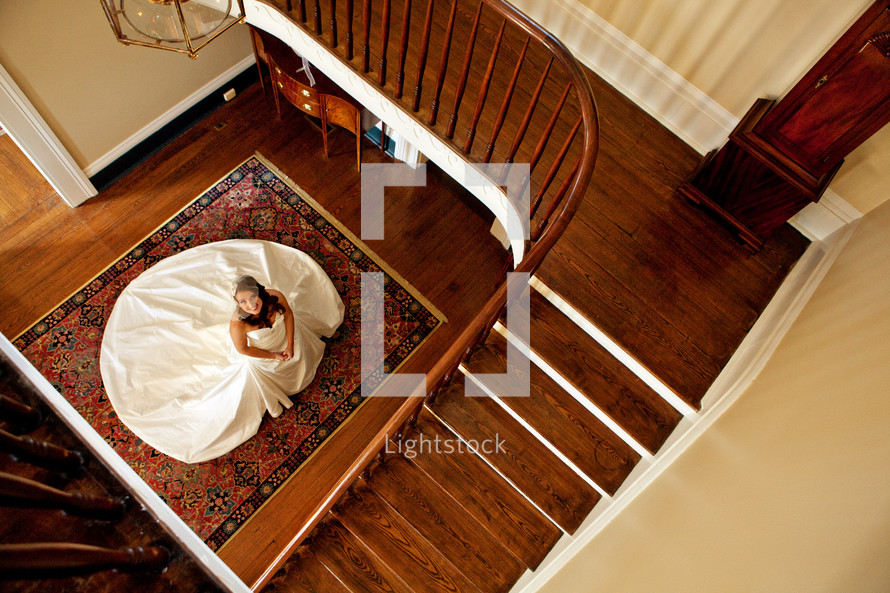 A bride in her wedding dress looking up the stairs