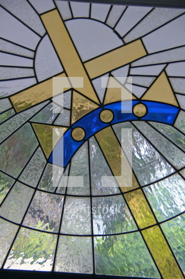 Stained glass window. Christ cross and King's crown.