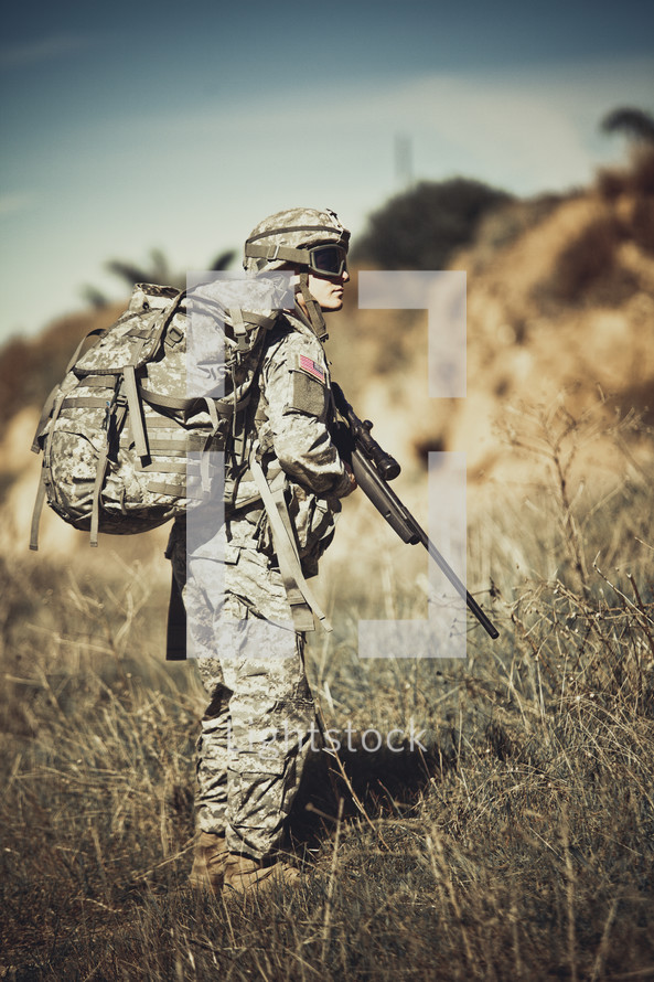 army soldier in the field holding a rifle