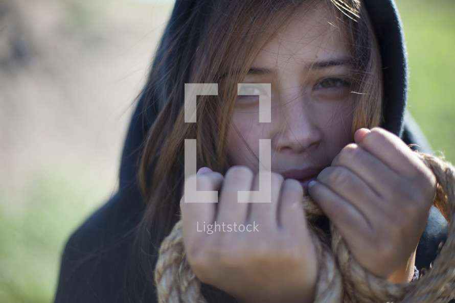 shrouded woman with her hands tied in rope