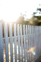 Sun shining through a white picket fence.
