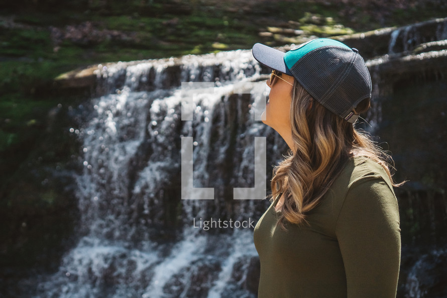 a woman in a ball cap standing outdoors by a waterfall