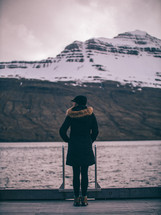 a woman standing on a dock looking out at the water