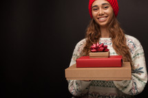a woman holding a stack of Christmas gifts