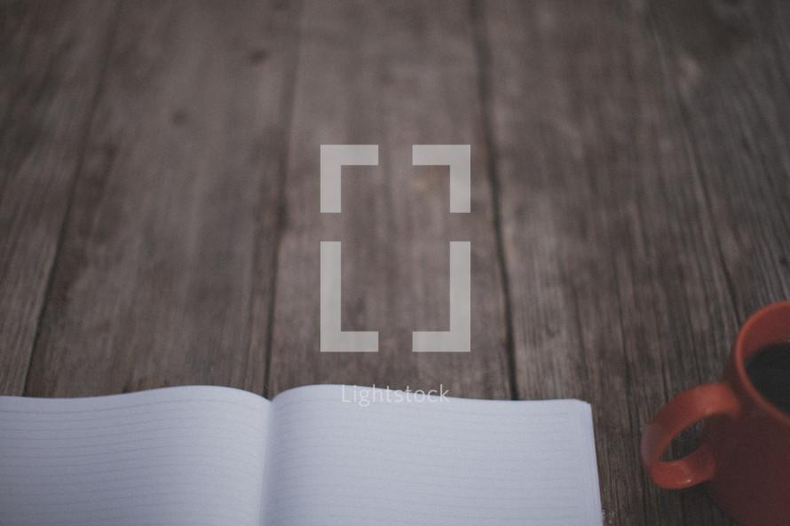 An open notebook and orange coffee mug