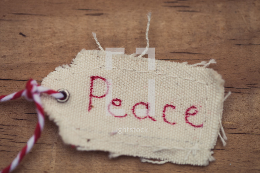 """A Christmas gift tag labeled """"Peace"""", against a wood grain background."""