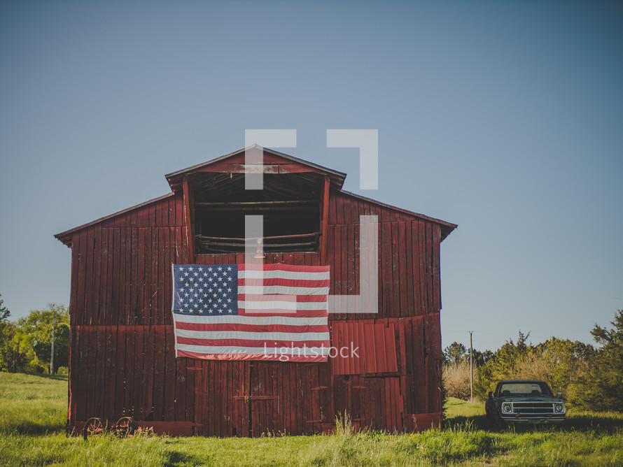 American flag draped over a red barn