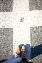 Feet on the pavement in an intersection.
