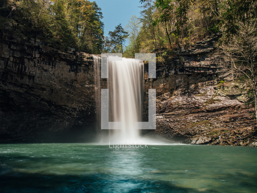 waterfall flowing over a cliff into a swimming hole