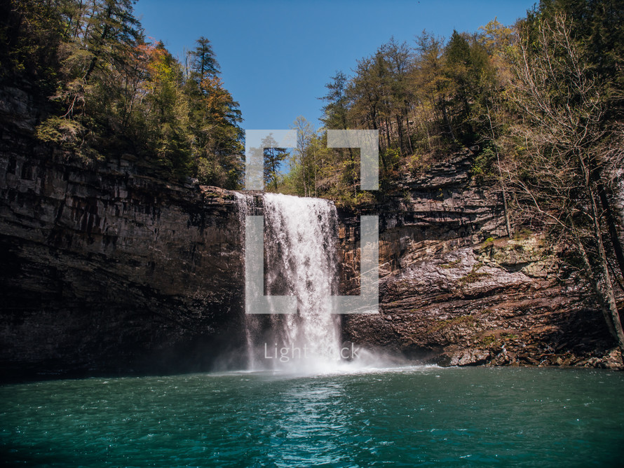 waterfall over the side of a cliff into a swimming hole