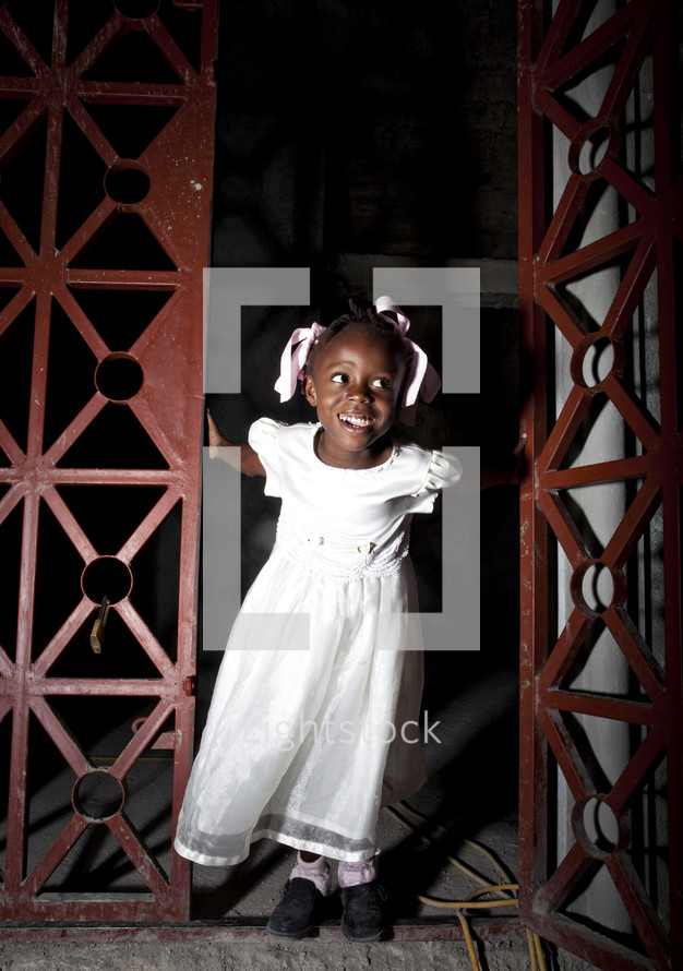 Smiling girl in white dress emerging from doorway.