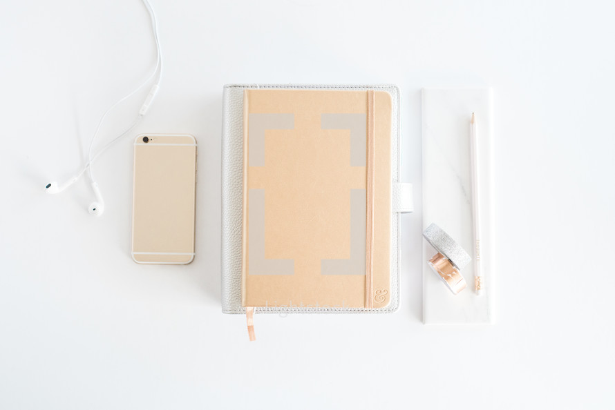 iPhone, journal, earbuds, and pencil on a white desk
