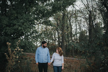 a couple holding hands outdoors, in fall