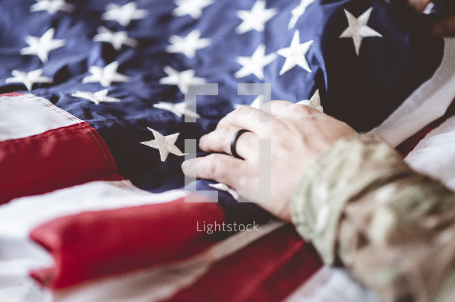 military man with hand on American flag