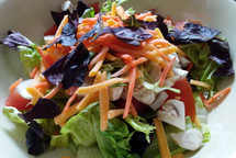A healthy salad with lettuce, carrots, cheese, tomato and other vegetables to make a healthy meal.