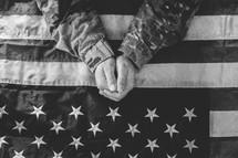 serviceman in uniform praying over an American flag