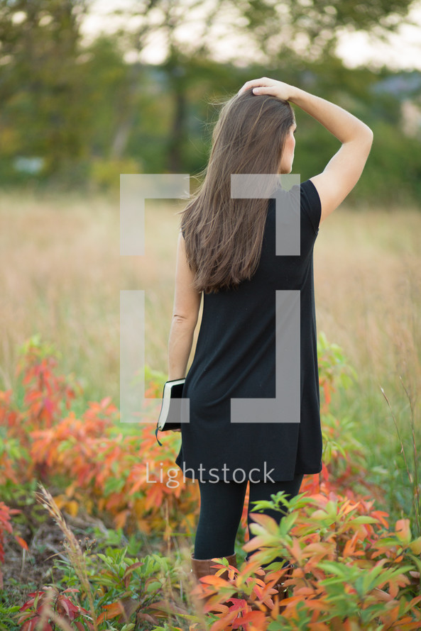 woman in a field holding a Bible with her hand on her head