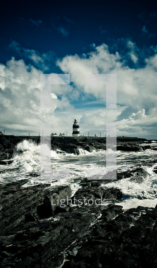 waves crashing into a rock wall near a lighthouse
