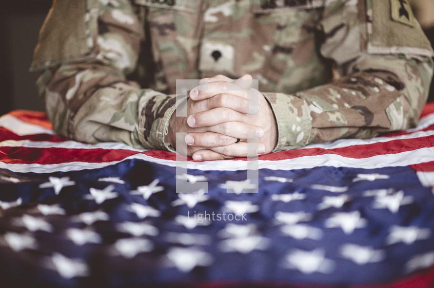 serviceman praying over an American flag