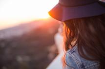woman in a hat standing in sunlight