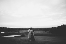 a couple hugging outdoors in black and white