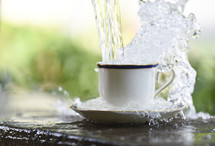 Water being poured and overflowing from a cup and saucer.