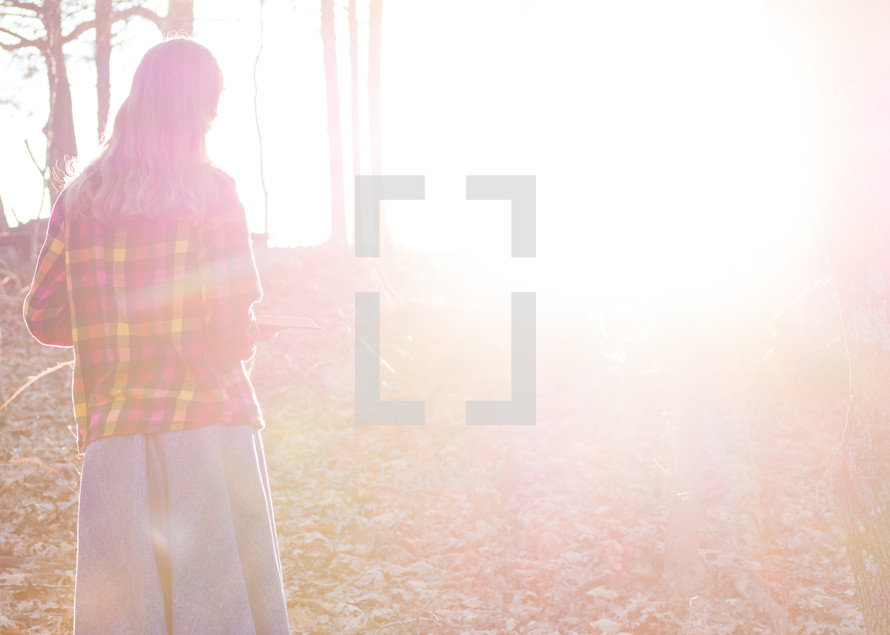 A woman in a long skirt standing in bright sunlight