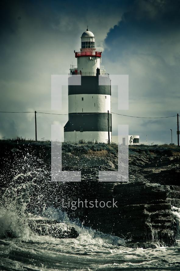 waves crashing into to a wall near a lighthouse