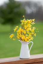 yellow flowers in a pitcher on wood railing