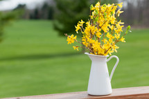 yellow flowers in a pitcher on a wood railing