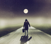a man in a top hat walking on a road carrying luggage under a full moon