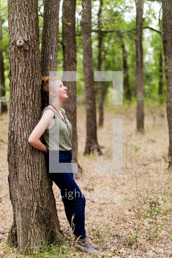 woman leaning on a tree outdoors