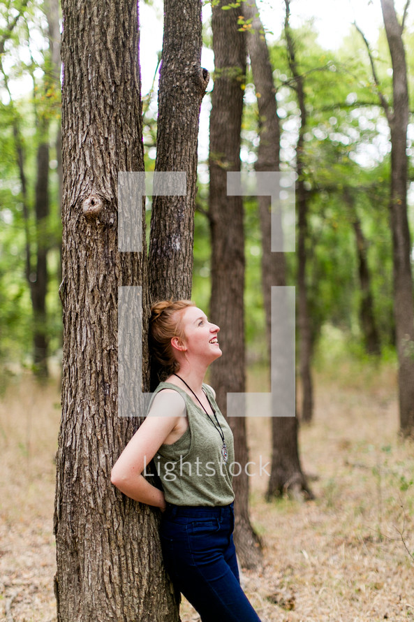 woman leaning on a tree in a forest
