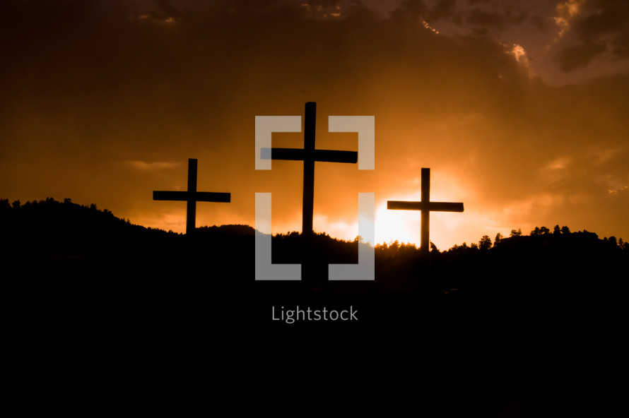 sun setting behind three crosses