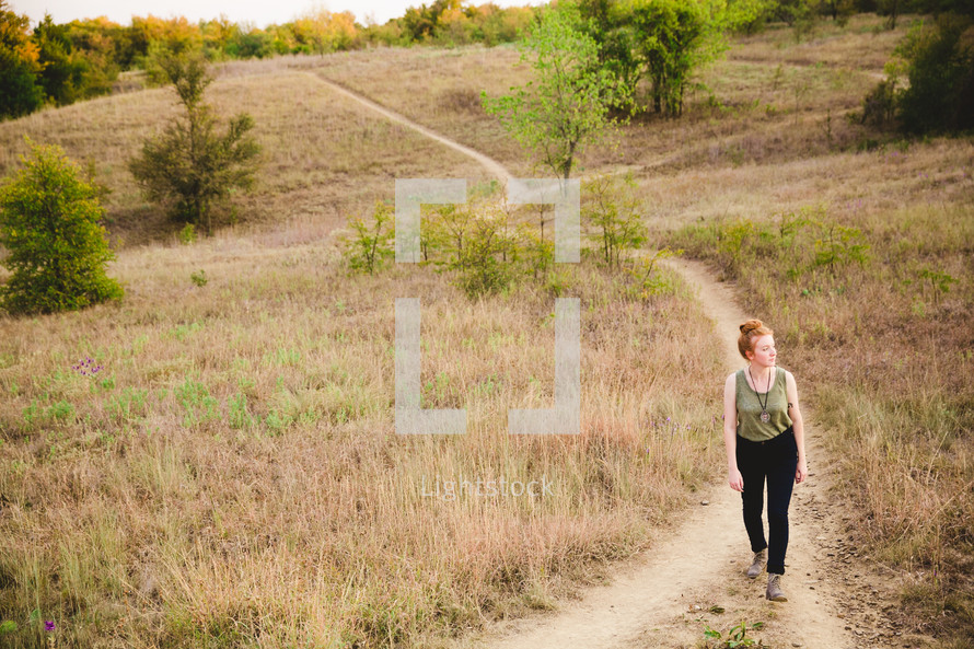 woman walking on a path up a hill